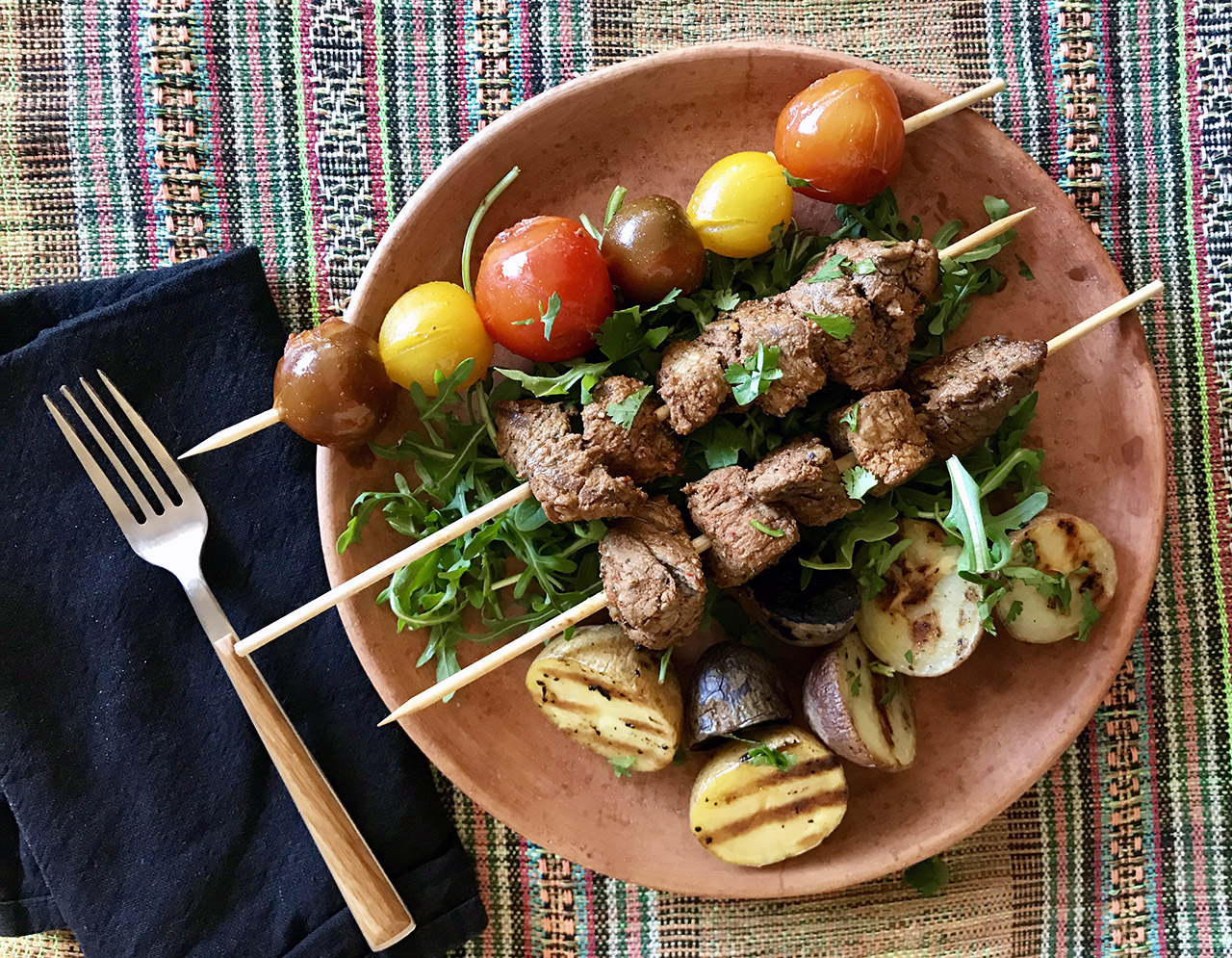 a clay-red plate with two skewers of beef cubes and one skewer of colorful small tomatoes