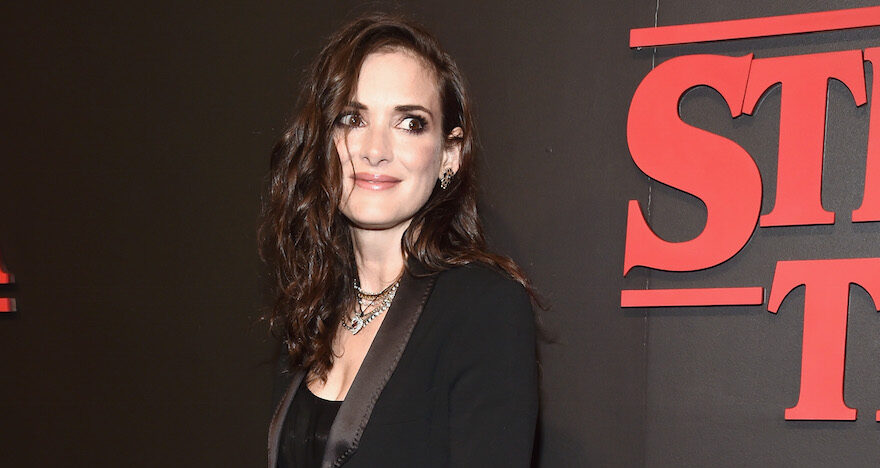 "Winona Ryder dressed in black with a ""Stranger Things"" sign behind her"