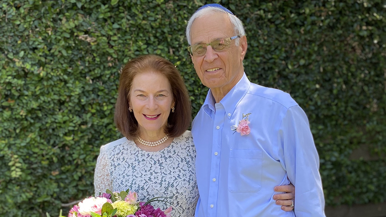 an older white couple standing together, smiling. she is wearing a white dress and holding a bouquet. he has a blue shirt with a flower pinned to it.