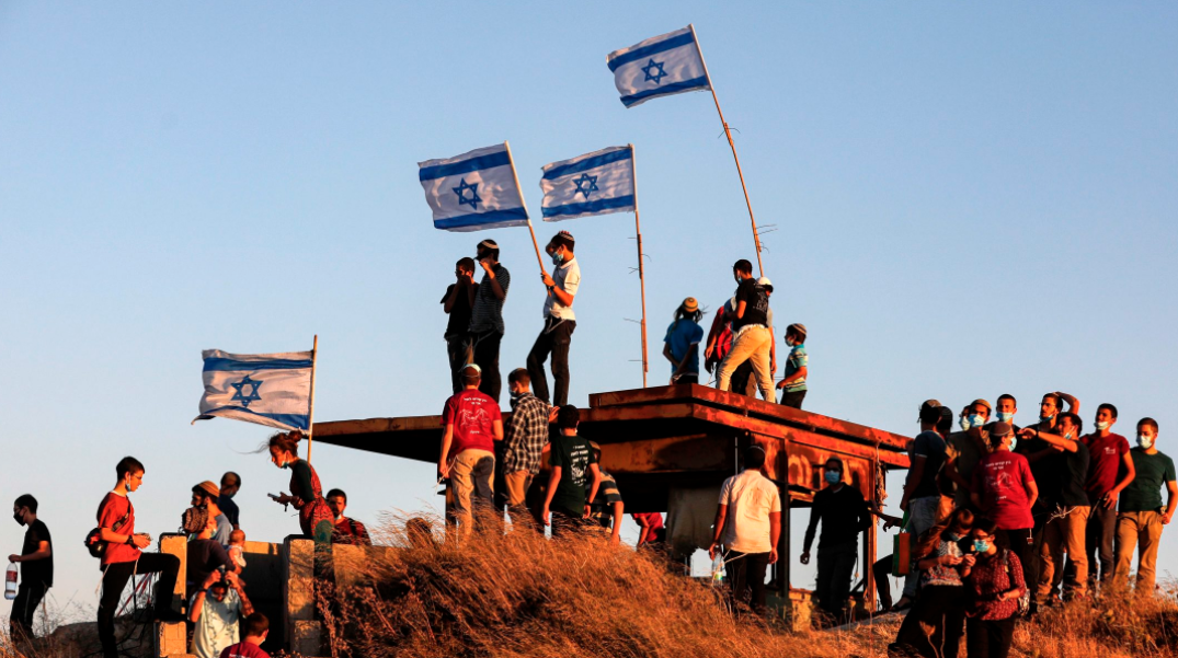 Several young men stand on top of a hill waving Israeli flags