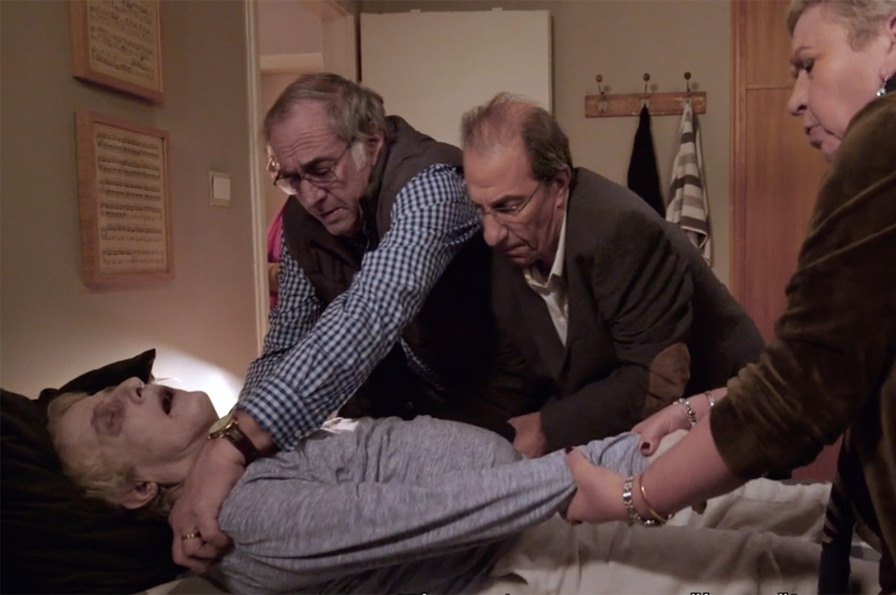 two older men and one older woman struggle to get the corpse of another older man out of bed