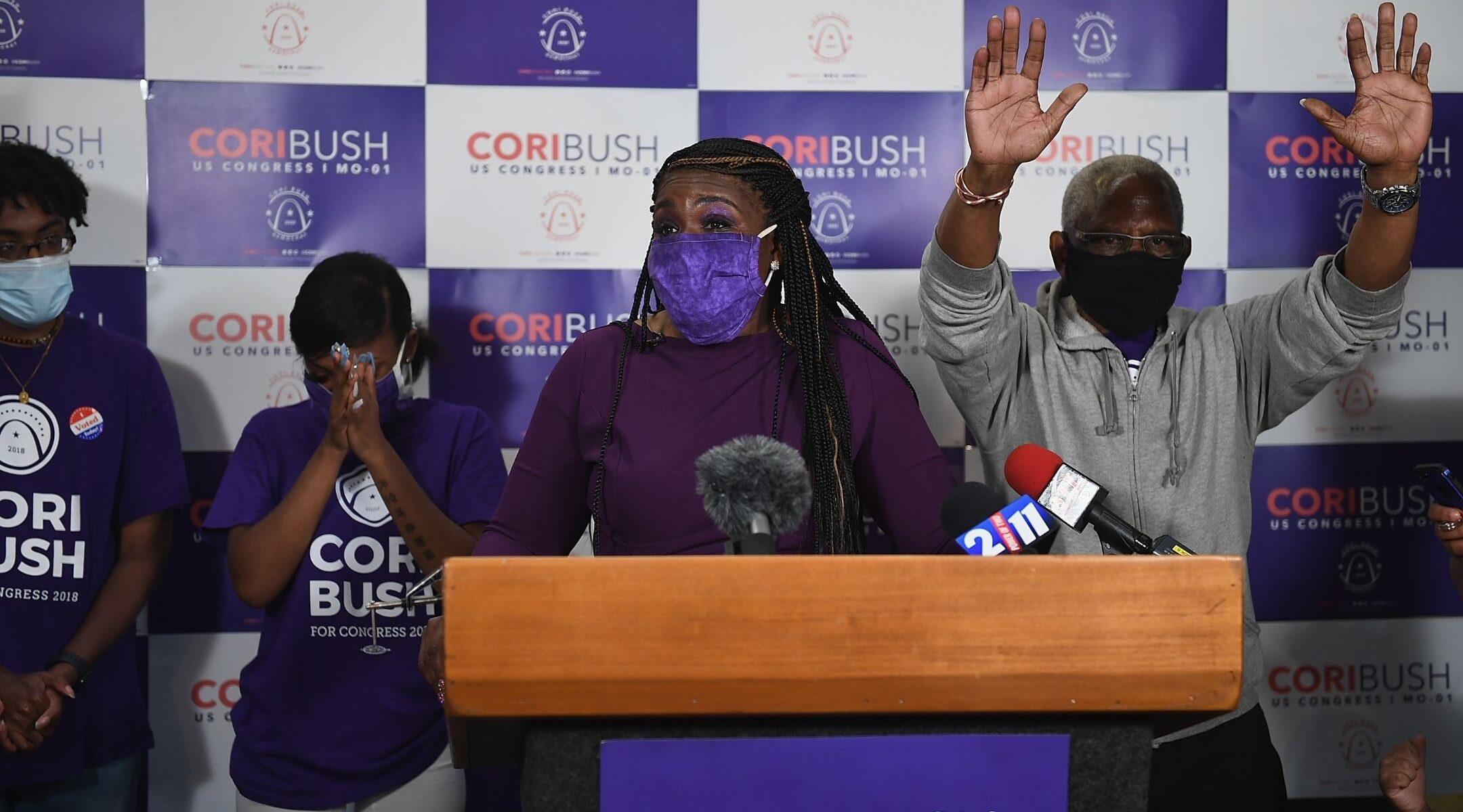 a black woman in a facemask speaks at a podium