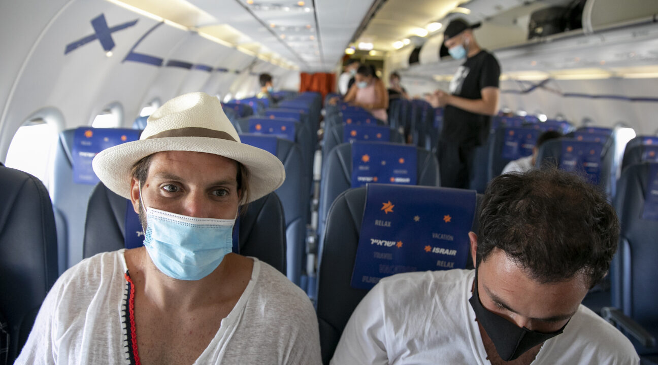 two men sit on an airplane wearing face masks