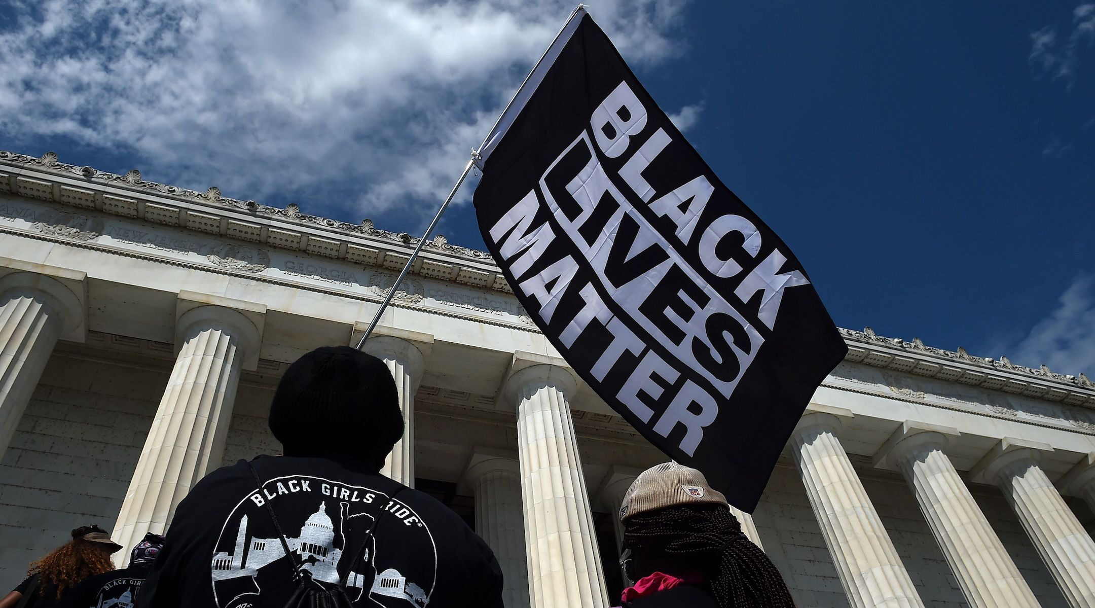 """A person holds a Black Lives Matter flag during the """"Commitment March: Get Your Knee Off Our Necks"""" protest against racism and police brutality, at the Lincoln Memorial in Washington, D.C., Aug. 28, 2020. (Photo/JTA-Olivier Douliery-Pool-AFP via Getty Images)"""