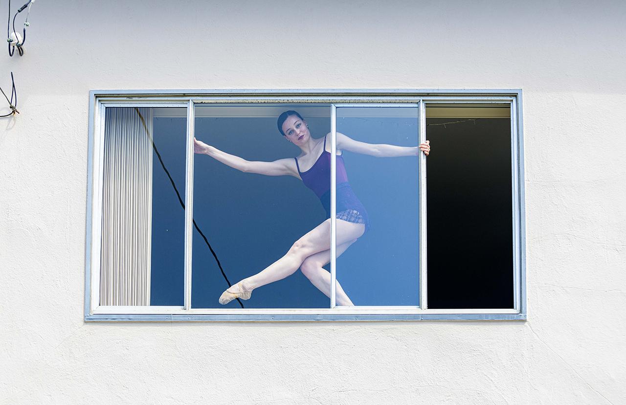 Ballerina Léna Alvino, seen through the window, dances in her bedroom. (Photo/Kyle Adler Photography)