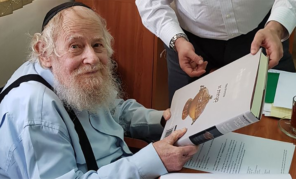 an old man with a beard holds a volume of Talmud