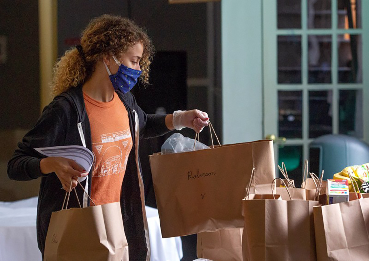 a young black woman wearing a facemask hefts brown bags of groceries