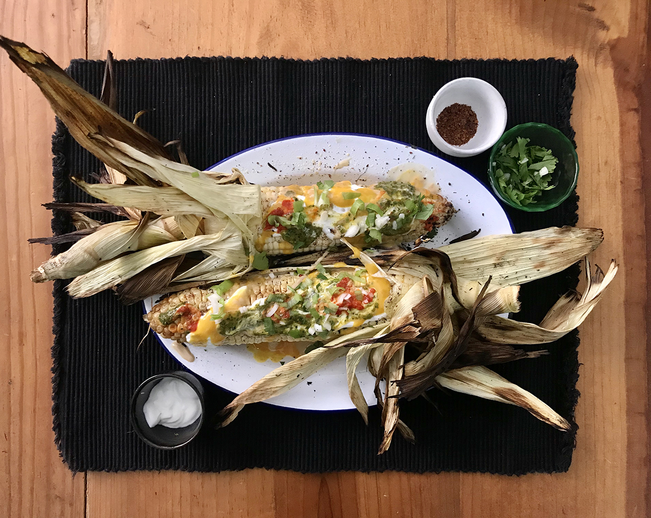 two grilled ears of corn on a white plate
