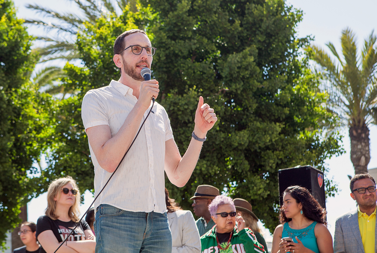 a man with a short beard and glasses holds a microphone and addresses a crowd outside
