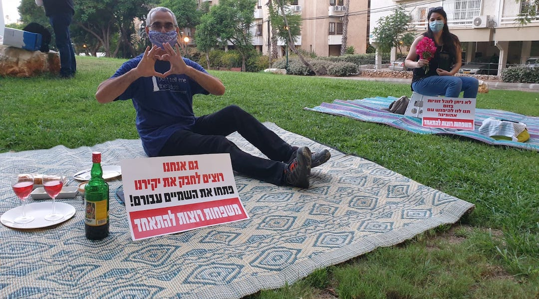 "Israelis protest being separated from their significant others outside the residence of the foreign minister by having solo romantic picnics on the eve of Tu B'Av, the Jewish day celebrating love. The signs read, ""We also want to embrace our loved ones. Open the skies for them. Families want to be together."" (Photo/ Courtesy Plia Kettner)"