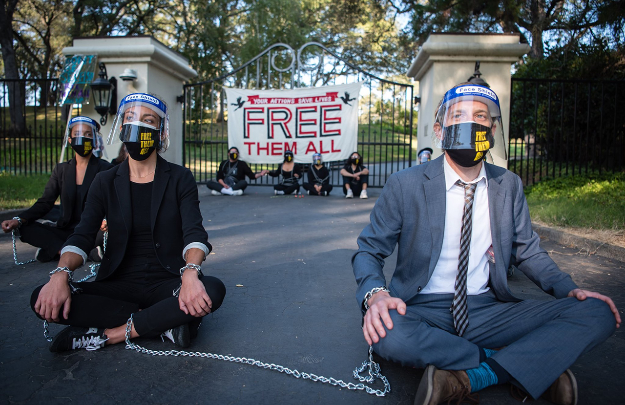 "several people wearing facemasks sit in chains protesting in front of a gate with a banner that says ""FREE THEM ALL"""