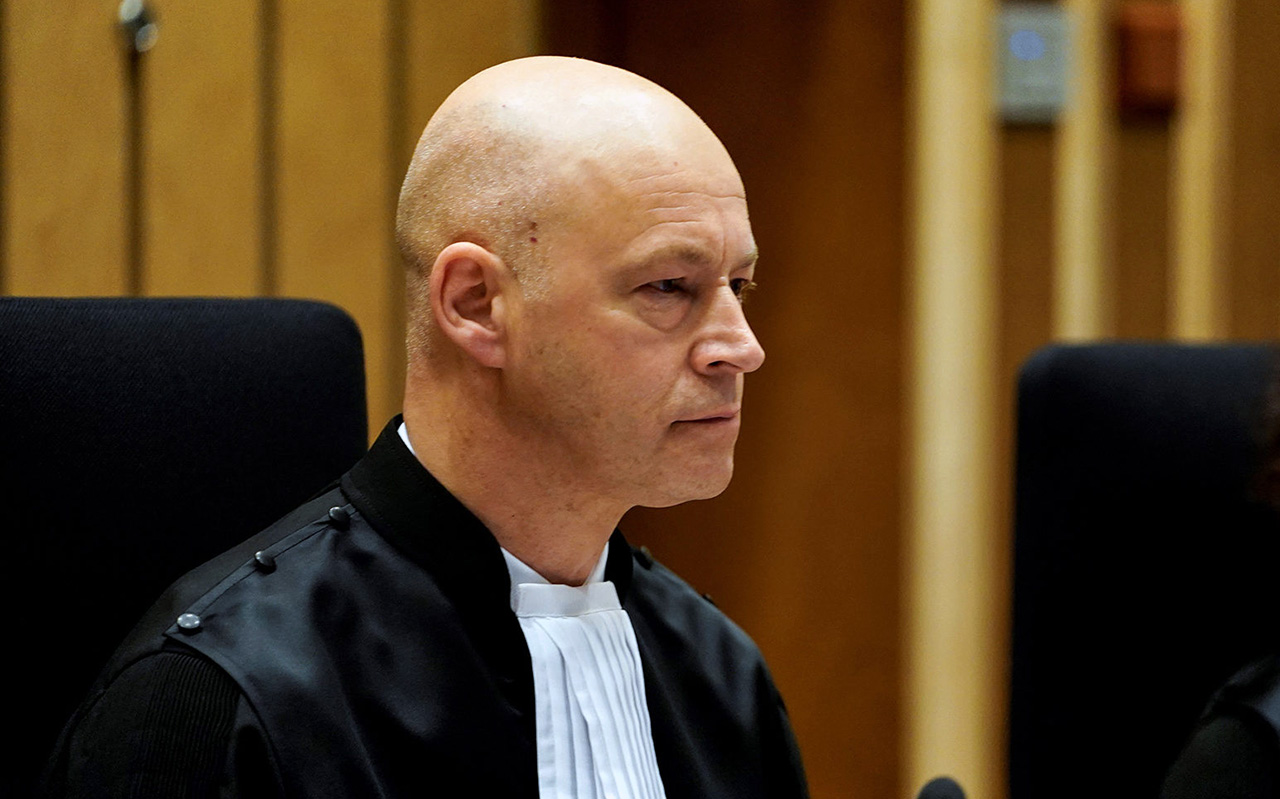 a bald man in a black judge's robe sits in a chair