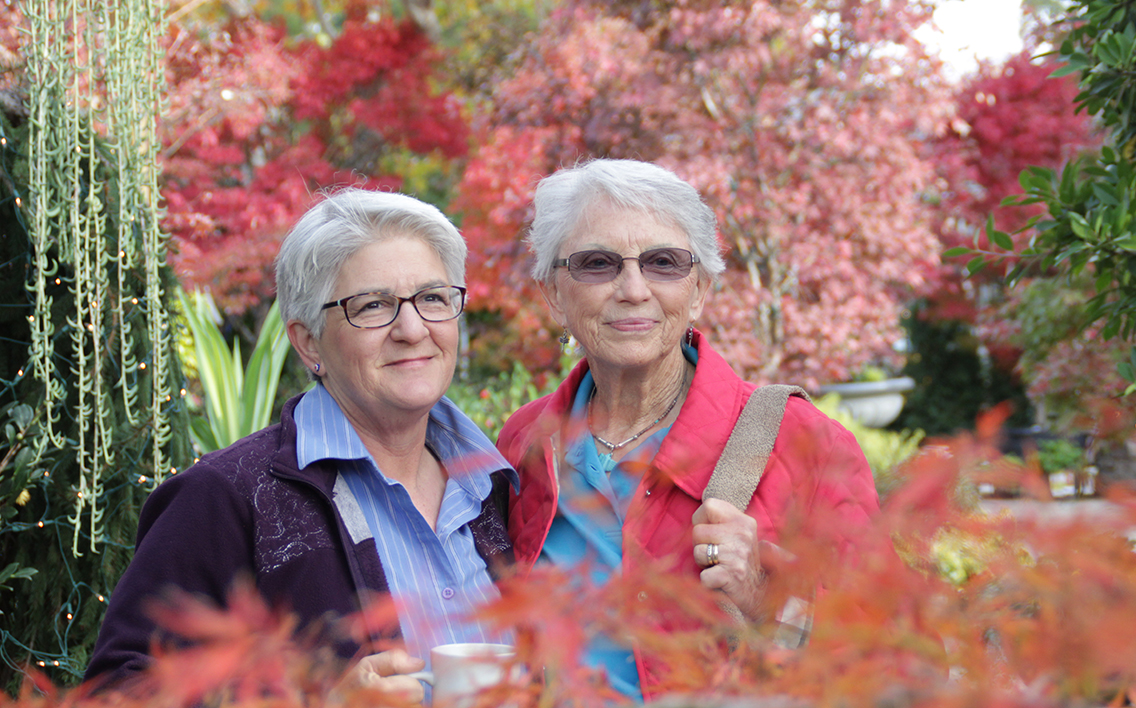 two old woman with short white hair pose together smiling