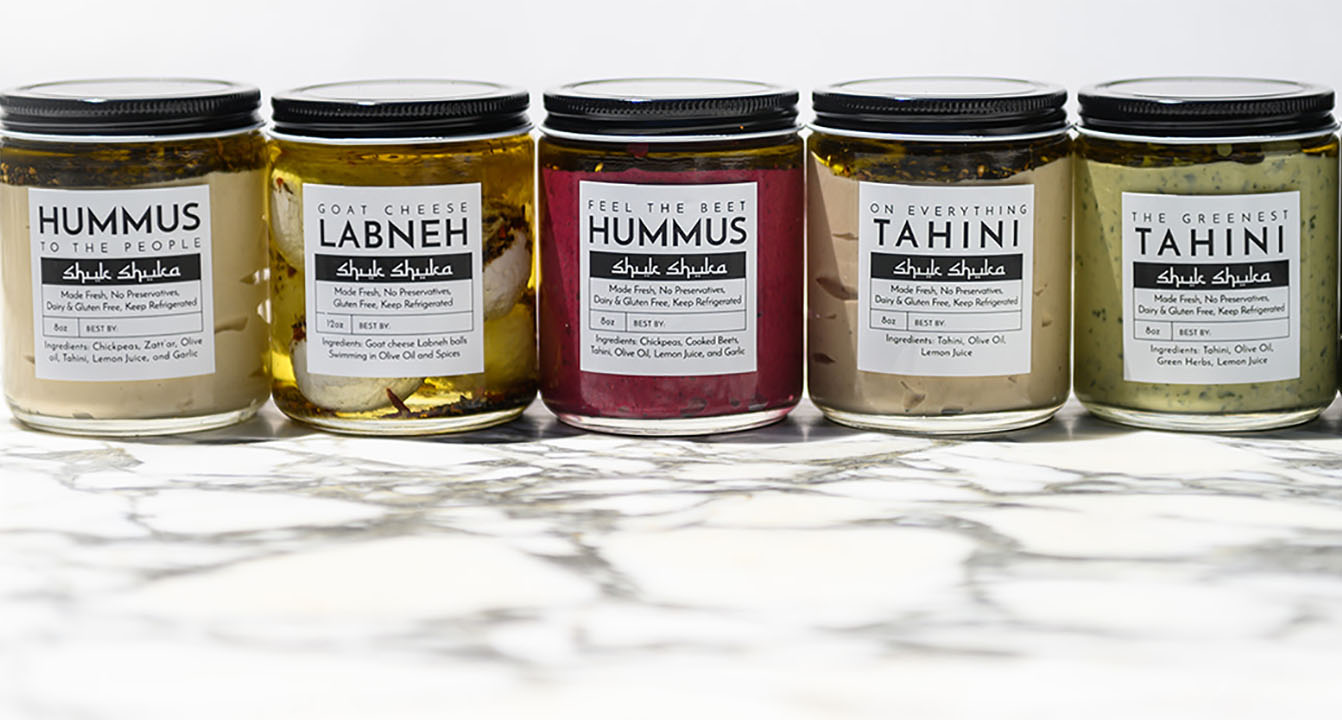An array of Shuk Shuka dips in refillable glass jars.