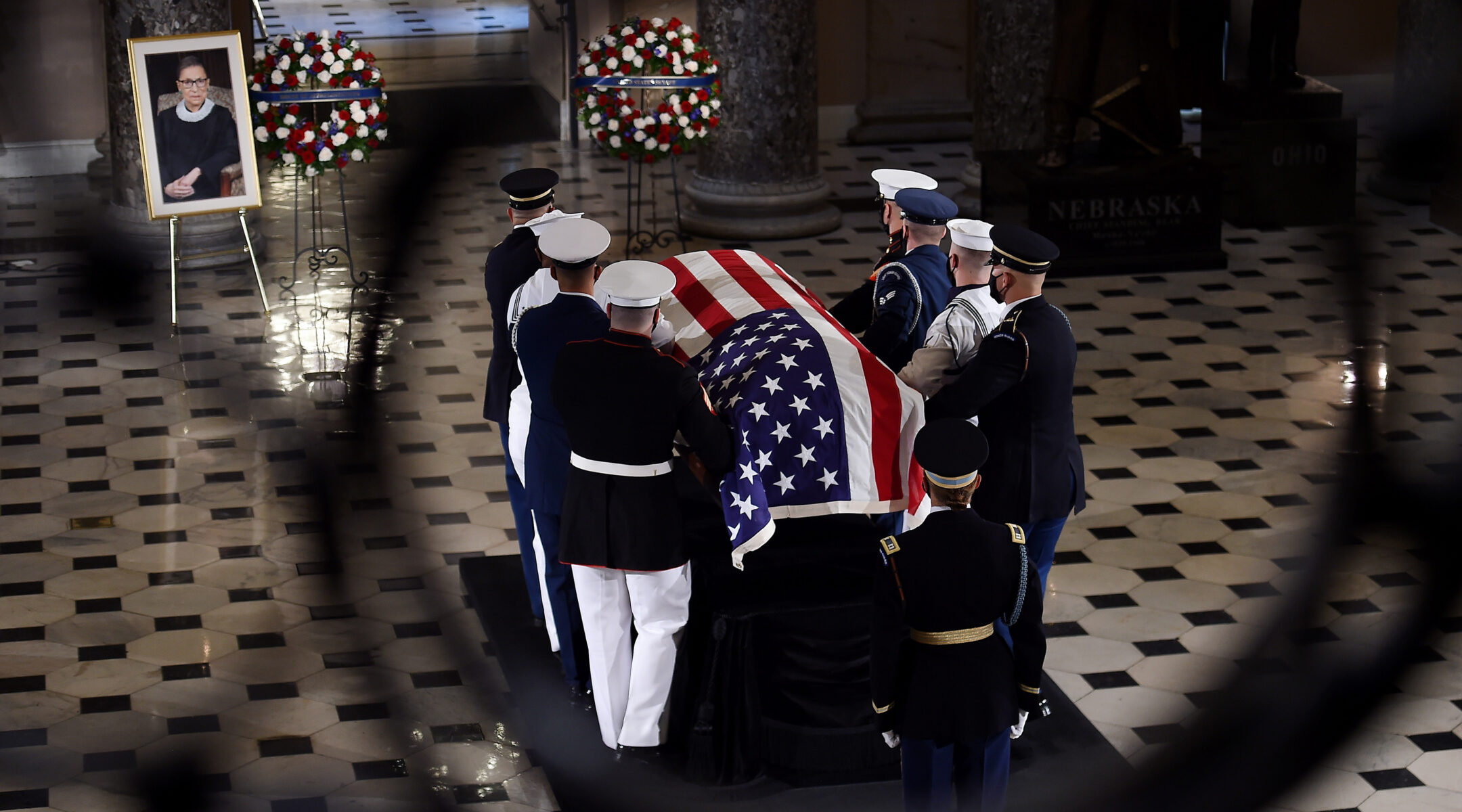 eight men in military uniform carry a casket draped in an American flag