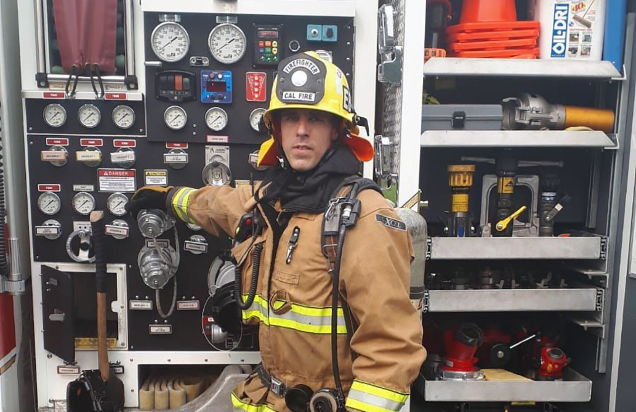 a man in full firefighter gear poses at the back of a firetruck with a grim expression
