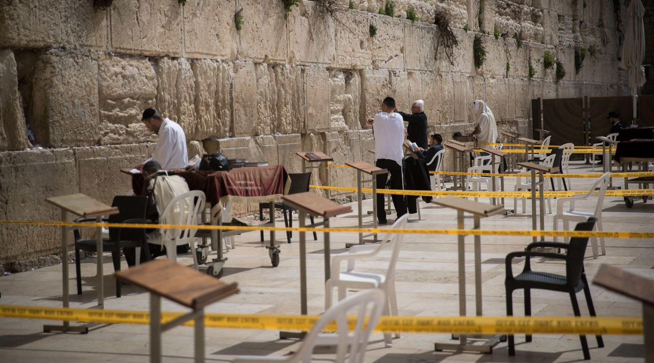 Worshippers at the Western Wall pray in enclosed areas meant for 10 people at a time in order to prevent the spread of coronavirus, March 15, 2020. (Photo/JTA-Yonatan Sindel-Flash90)