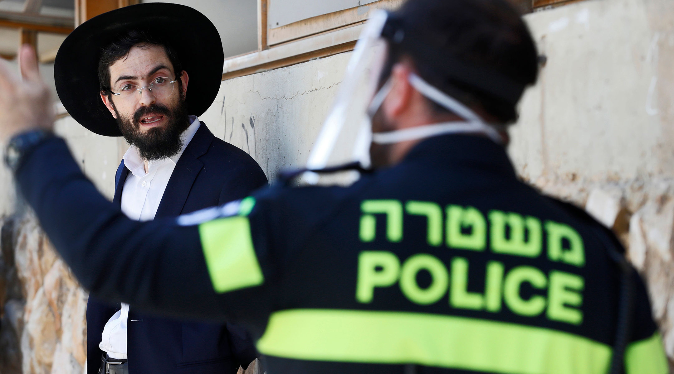 a police officer in a facemask speaks to an orthodox man in black suit and black hat but no facemask