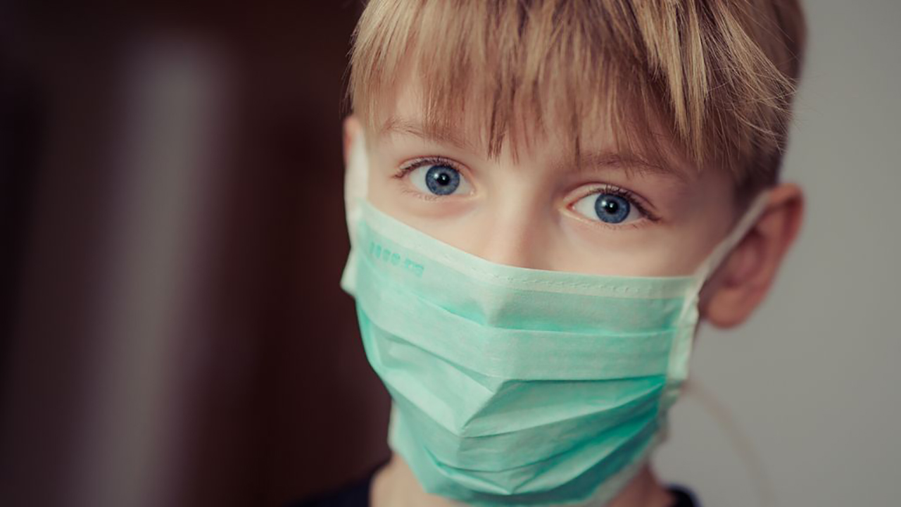 a blond boy wearing a facemask