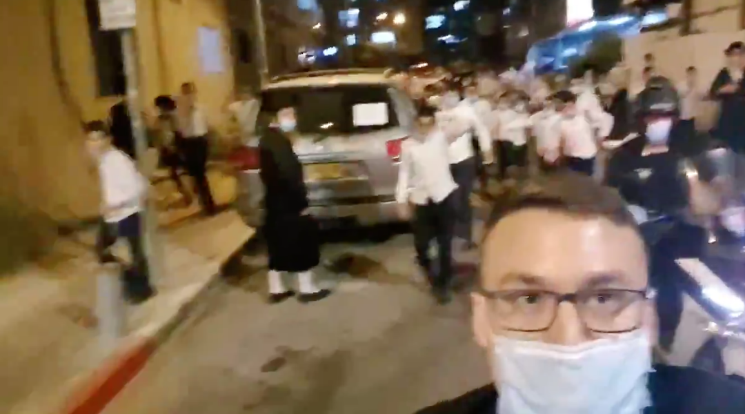 Reporter Ittai Shickman films himself chased by a mob of haredi Orthodox Jews while standing outside the home of a prominent rabbi in Bnei Brak, Israel. (Screenshot from Twitter)