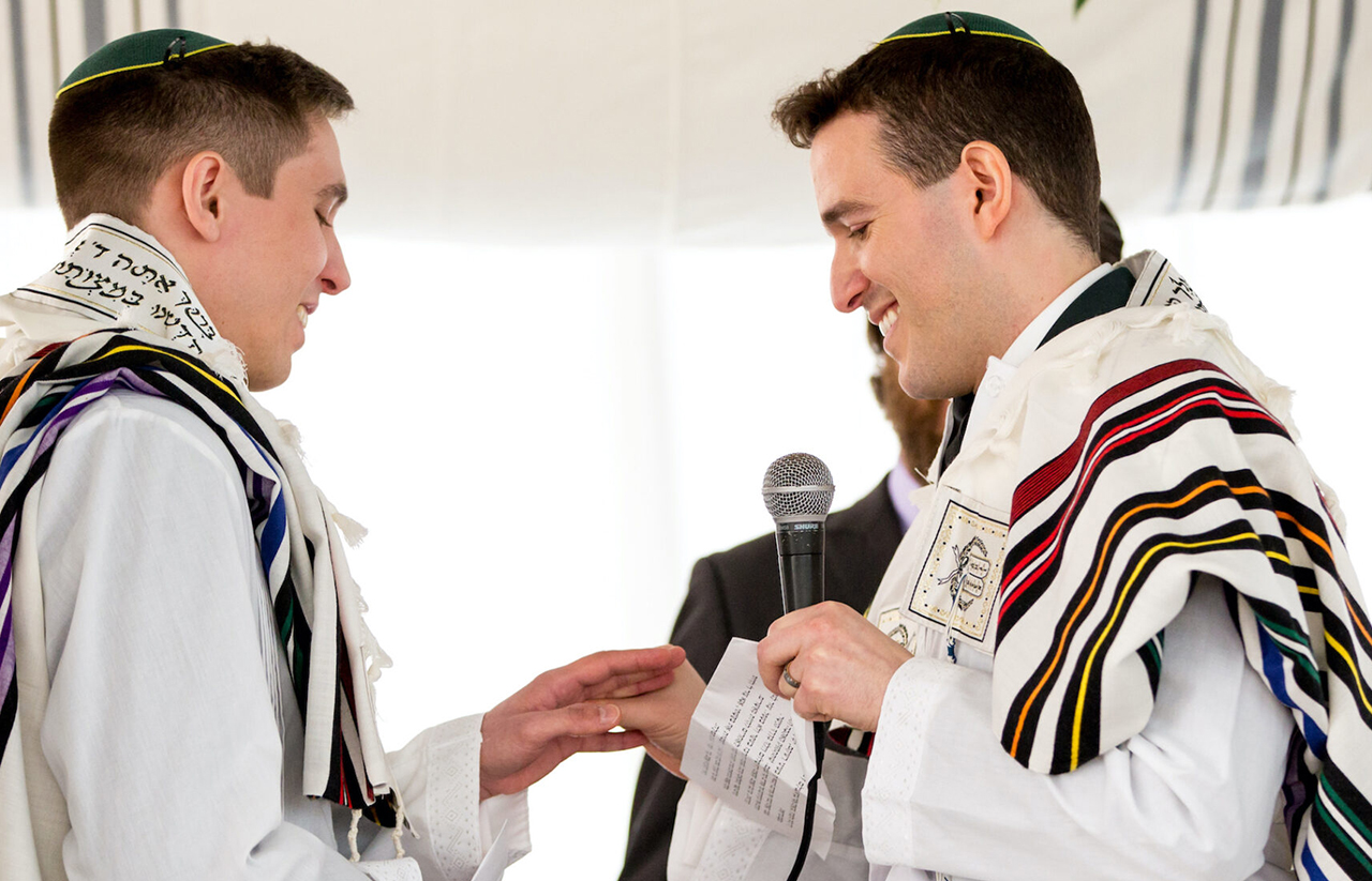 two young white men in rainbow tallits exchange rings