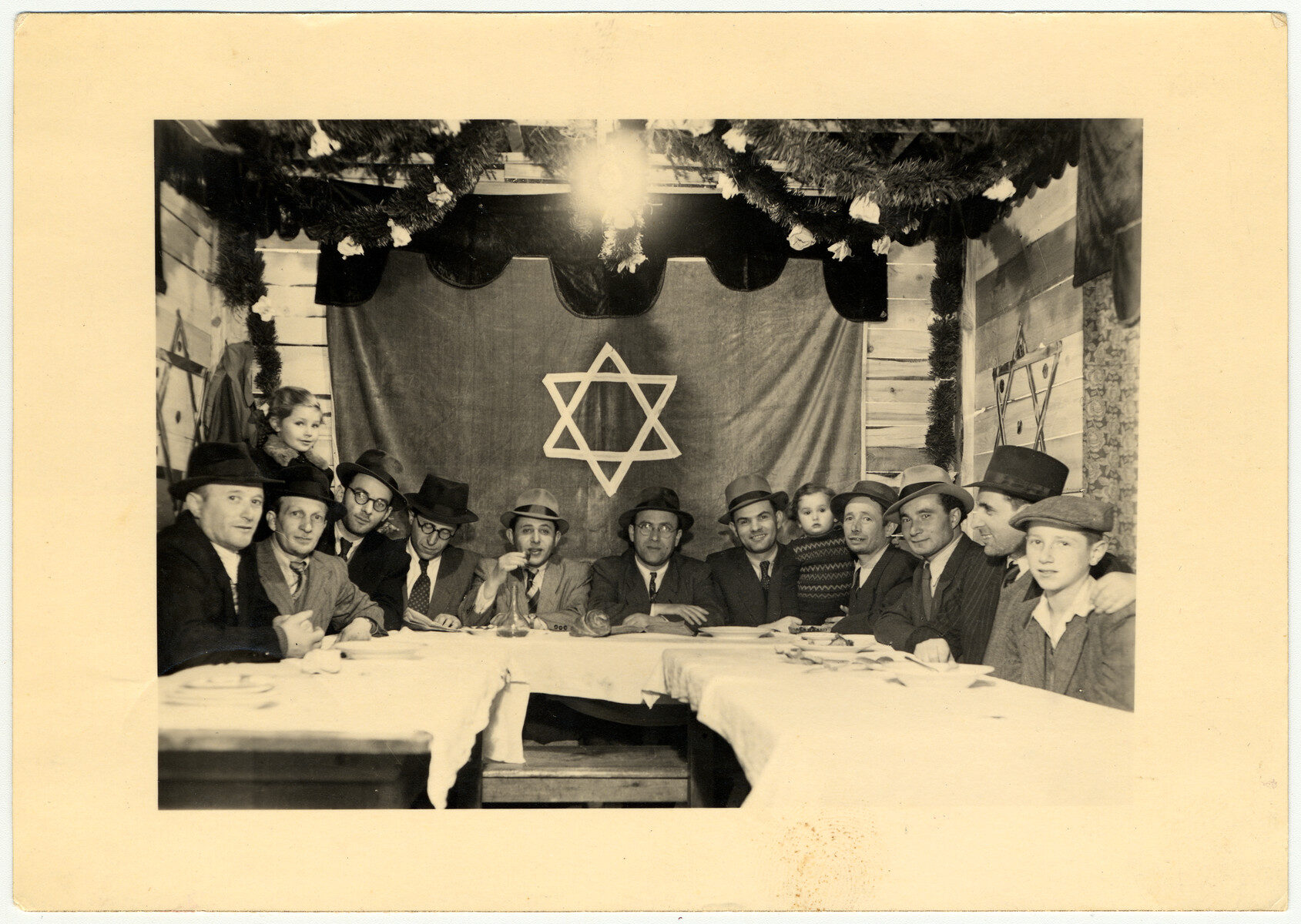 Jewish men gather in a communal sukkah in a displaced person's camp in Amberg, Germany, October 1947. (Photo/U.S. Holocaust Memorial Museum-Courtesy of Abraham Malach)