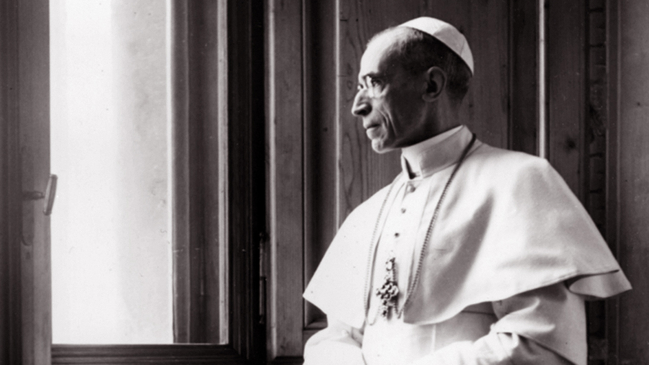 black and white: a thin older man in white papal robes gazes out a window