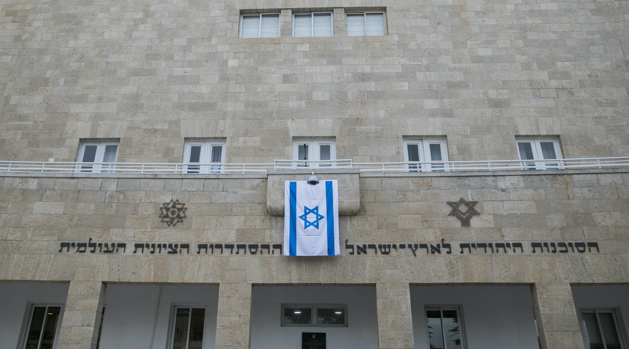 the facade of a plain limestone building with an Israeli flag hanging on it