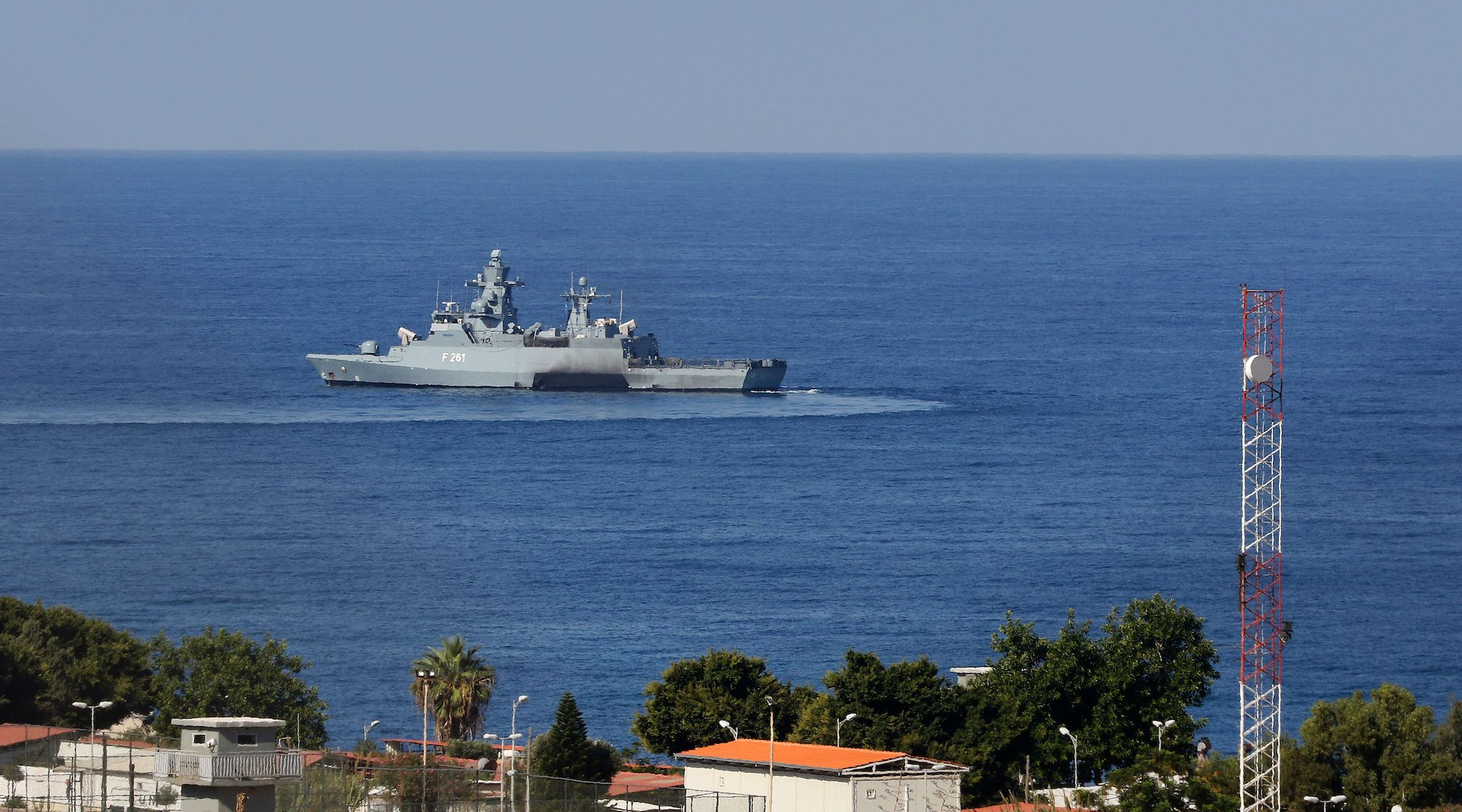 A view over some rooftops to the open sea and a grey military-looking vessel