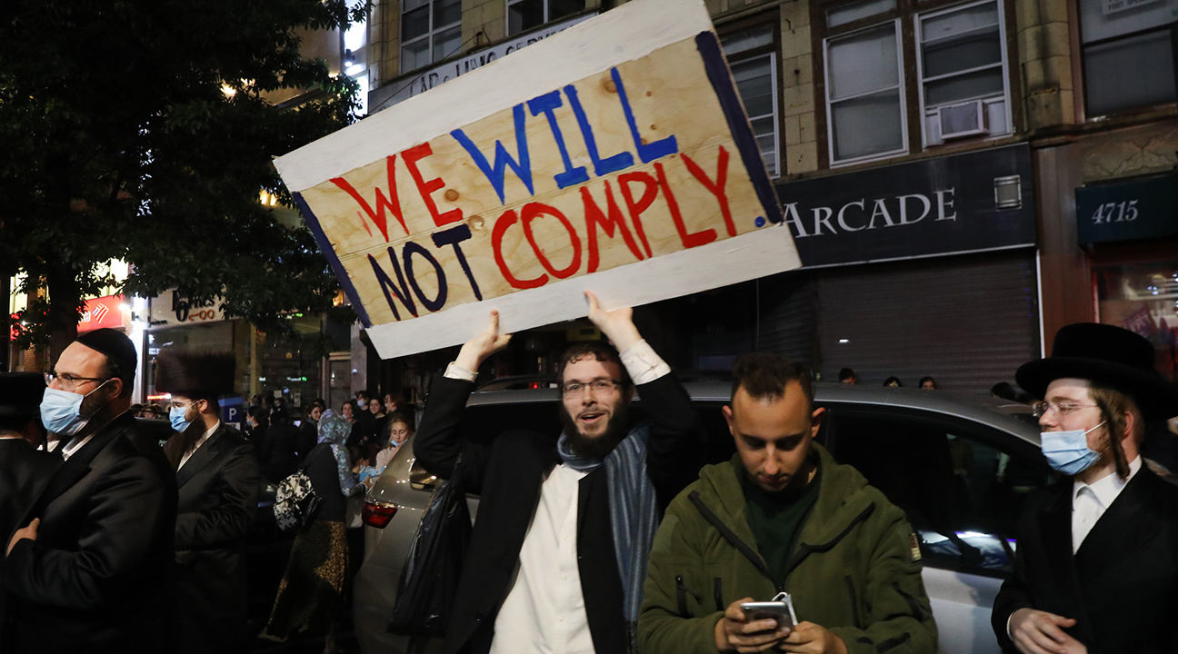 """a man in Hasidic garb in a large crowd holds up a hand-made sign that says """"We will not comply."""""""