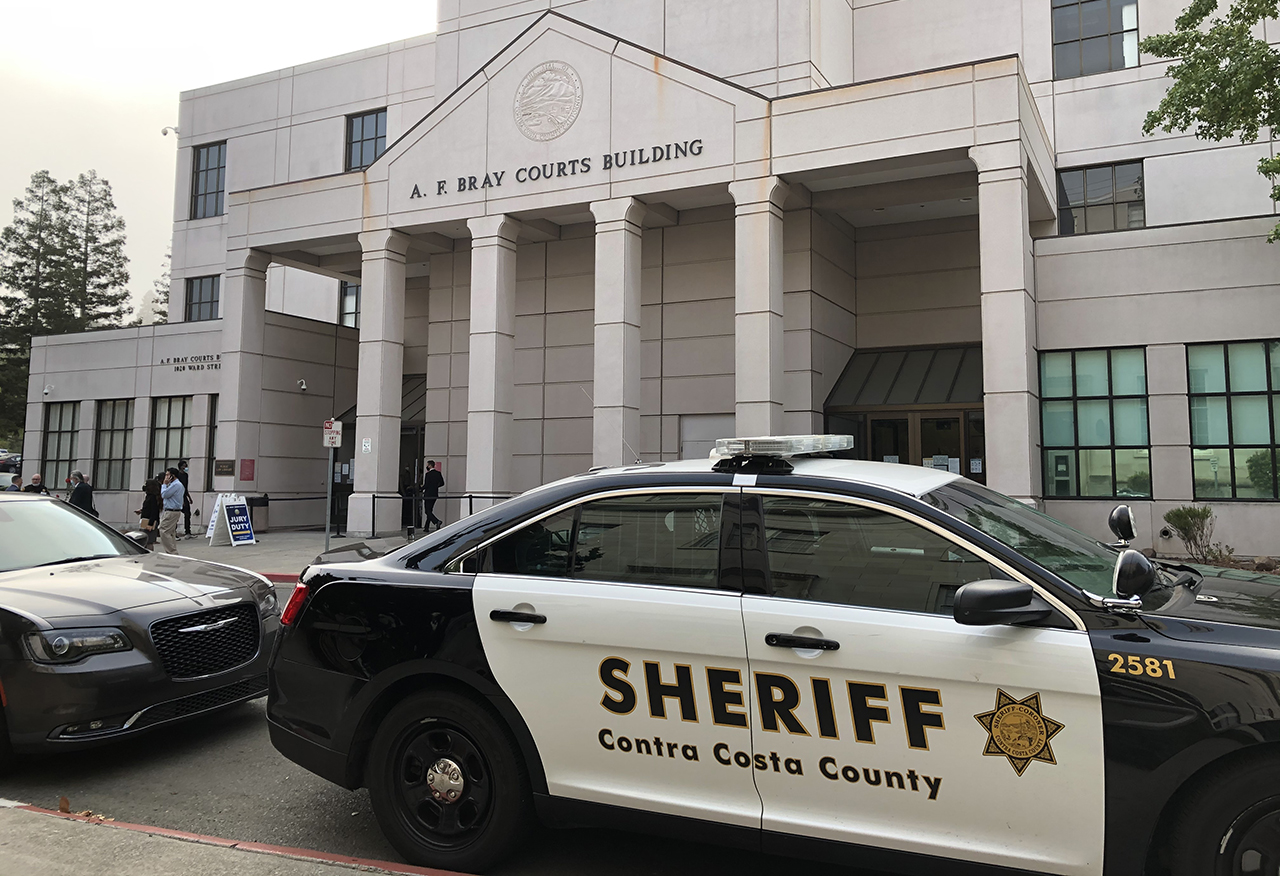 a Contra Costa County Sheriff car parked in front of a government office building