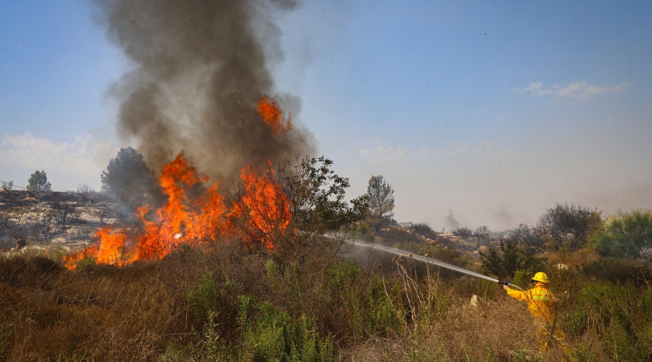 A firefighter works to extinguish a fire near the Kfar HaOranim settlement in the West Bank on Oct. 9, 2020. (Photo/JTA-Yossi Aloni-Flash90)