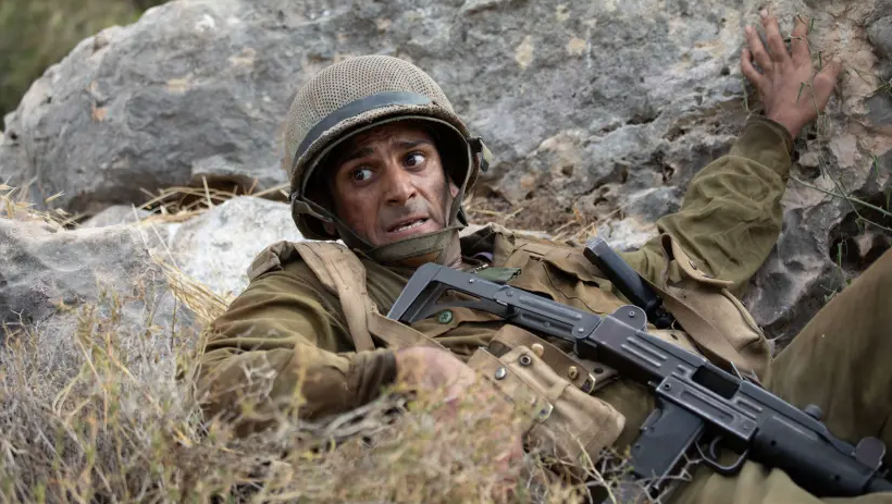 a scared young soldier crouches behind a rock holding a machine gun
