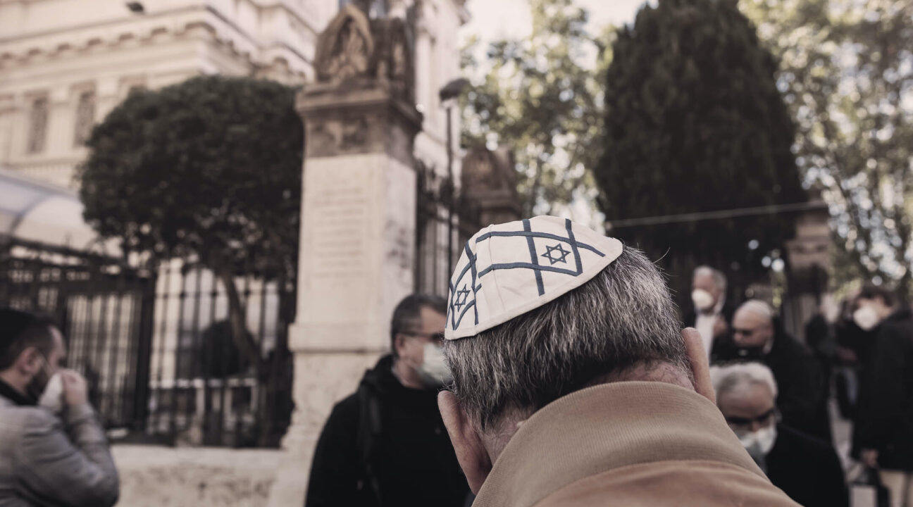 an old man outside with an Israeli flag kippah on his head