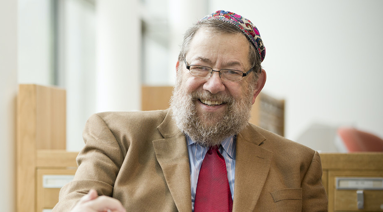 a seated smiling old man with a beard and colorful kippah
