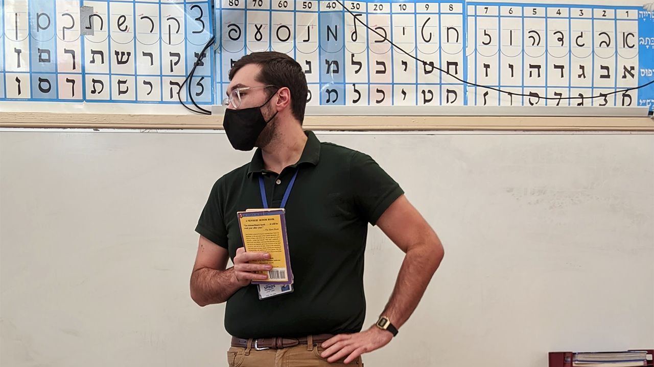 a white man with a black mask over her nose and mouth stands at the front of a classroom