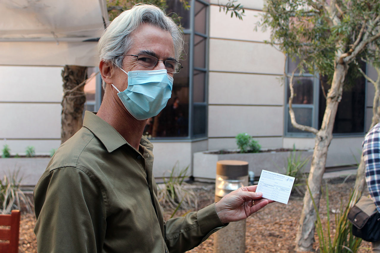 """Dr. Stephen Hall smiles with his """"Covid-19 Vaccination Record Card"""" after receiving the Pfizer-BioNTech Covid-19 vaccine at San Francisco Campus for Jewish Living, Dec. 21, 2020. (Photo/Gabriel Greschler)"""