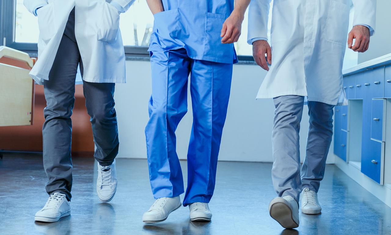 illustrative: three doctors walk toward the camera