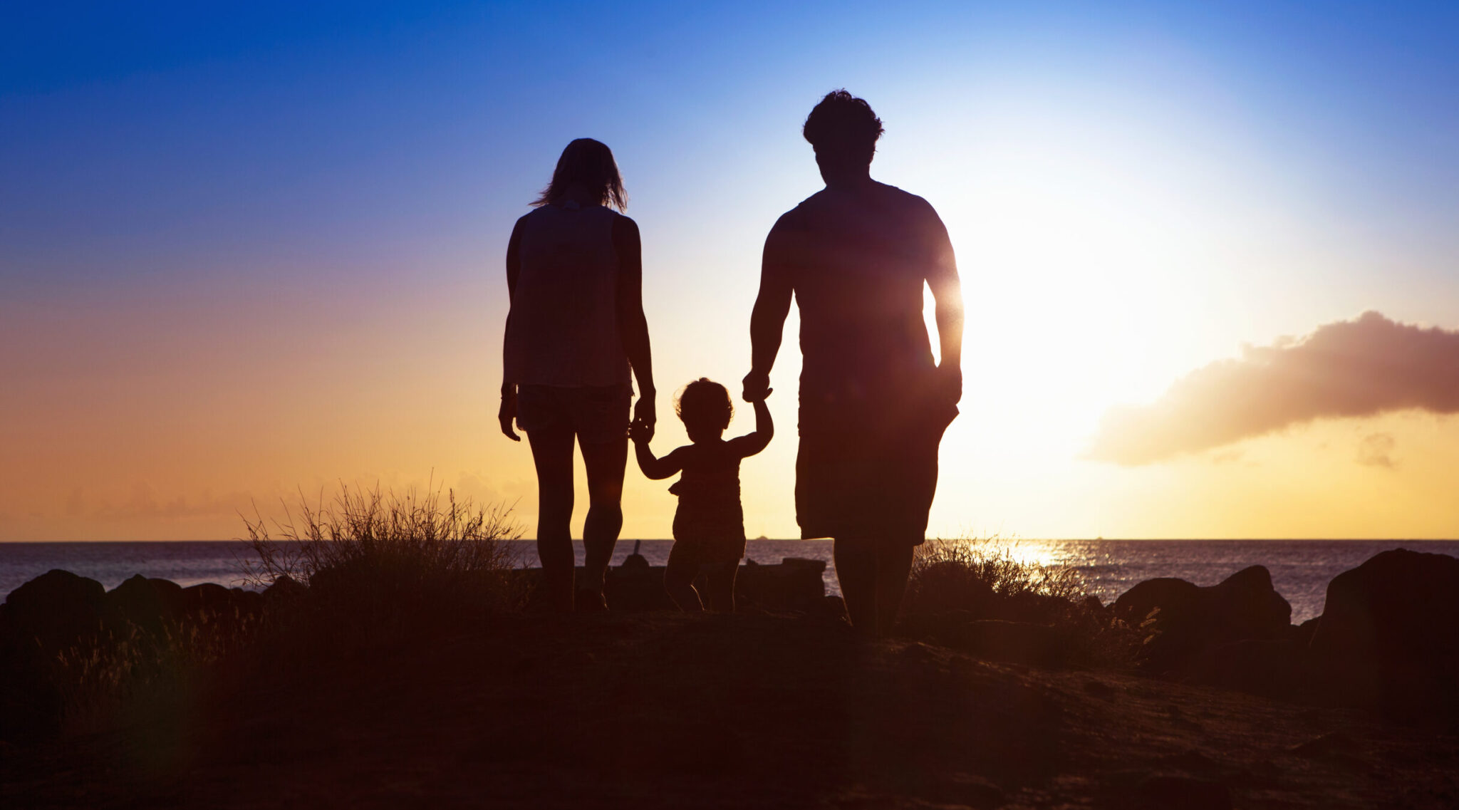 A family walks into the sunset on the beach with their young daughter