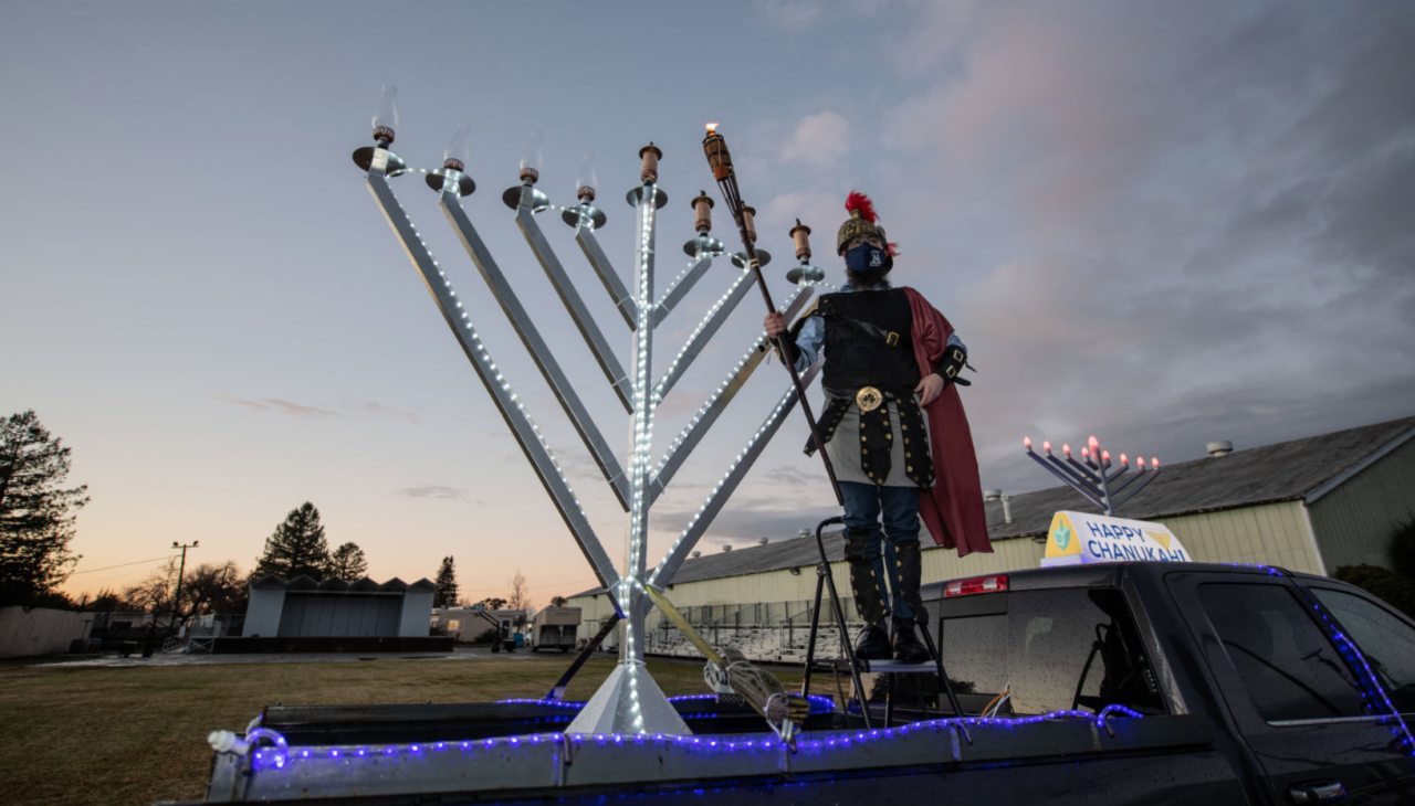 Rabbi Dovid Bush of Chabad of Petaluma lights the menorah at a Hanukkah drive-through event Dec. 13, which drew lines of cars and over 650 people. (Photo/Courtesy Bush)