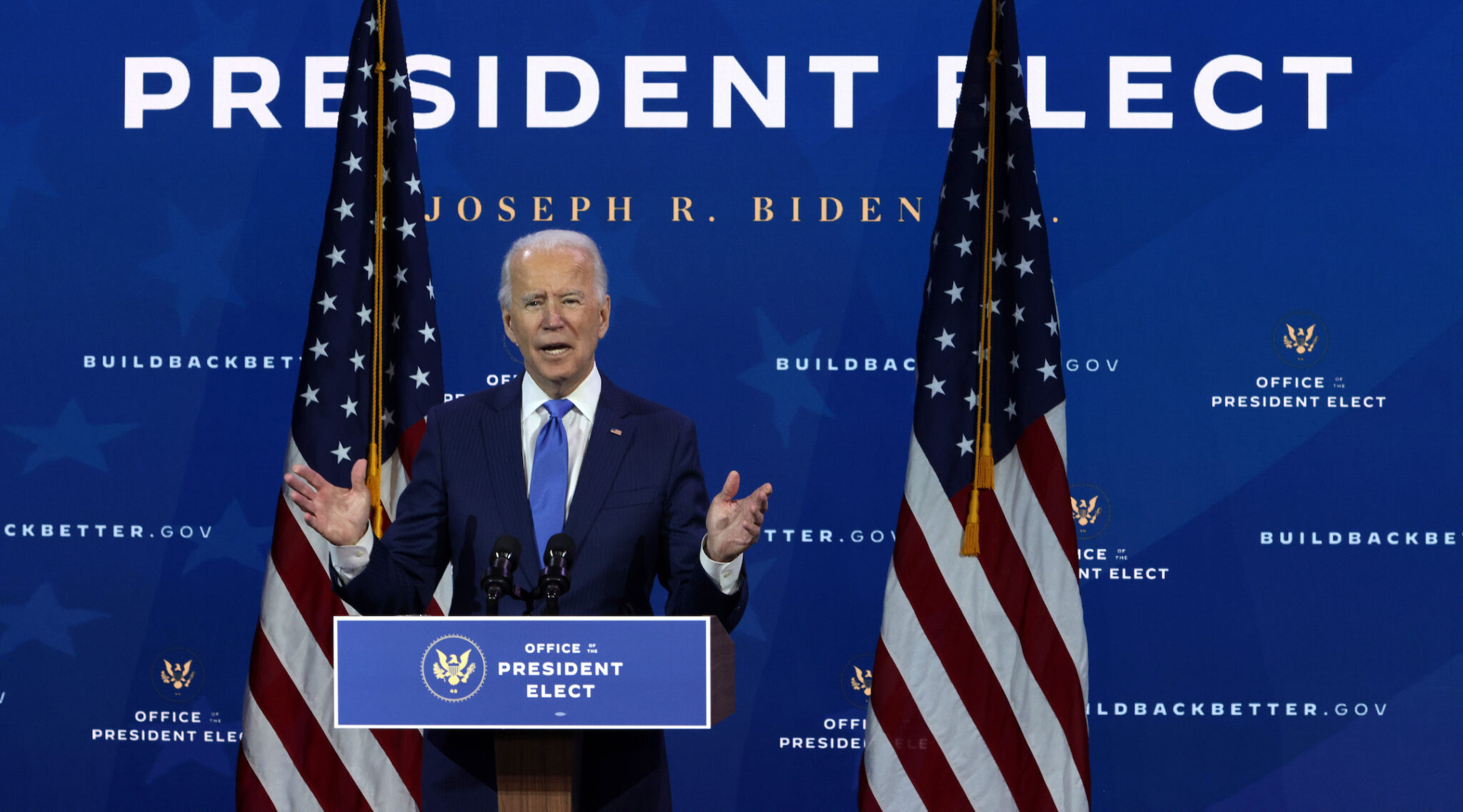 Biden speaks at a podium flanked by American flags