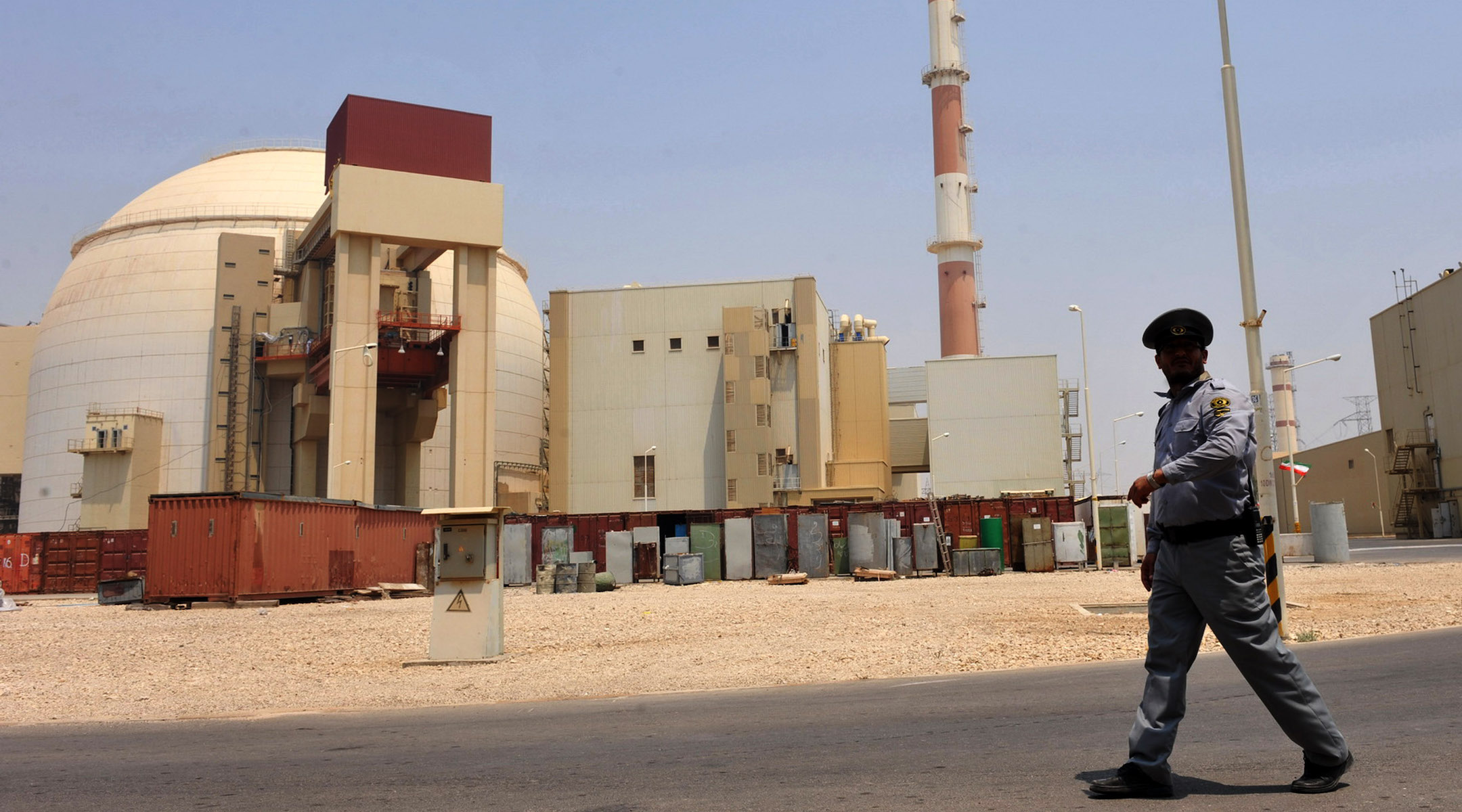 A soldier walks around outside a large dusty industrial facility