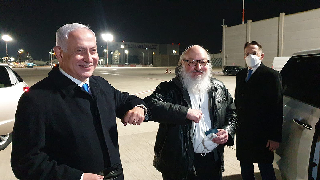 Two men bump elbows at Israeli airport