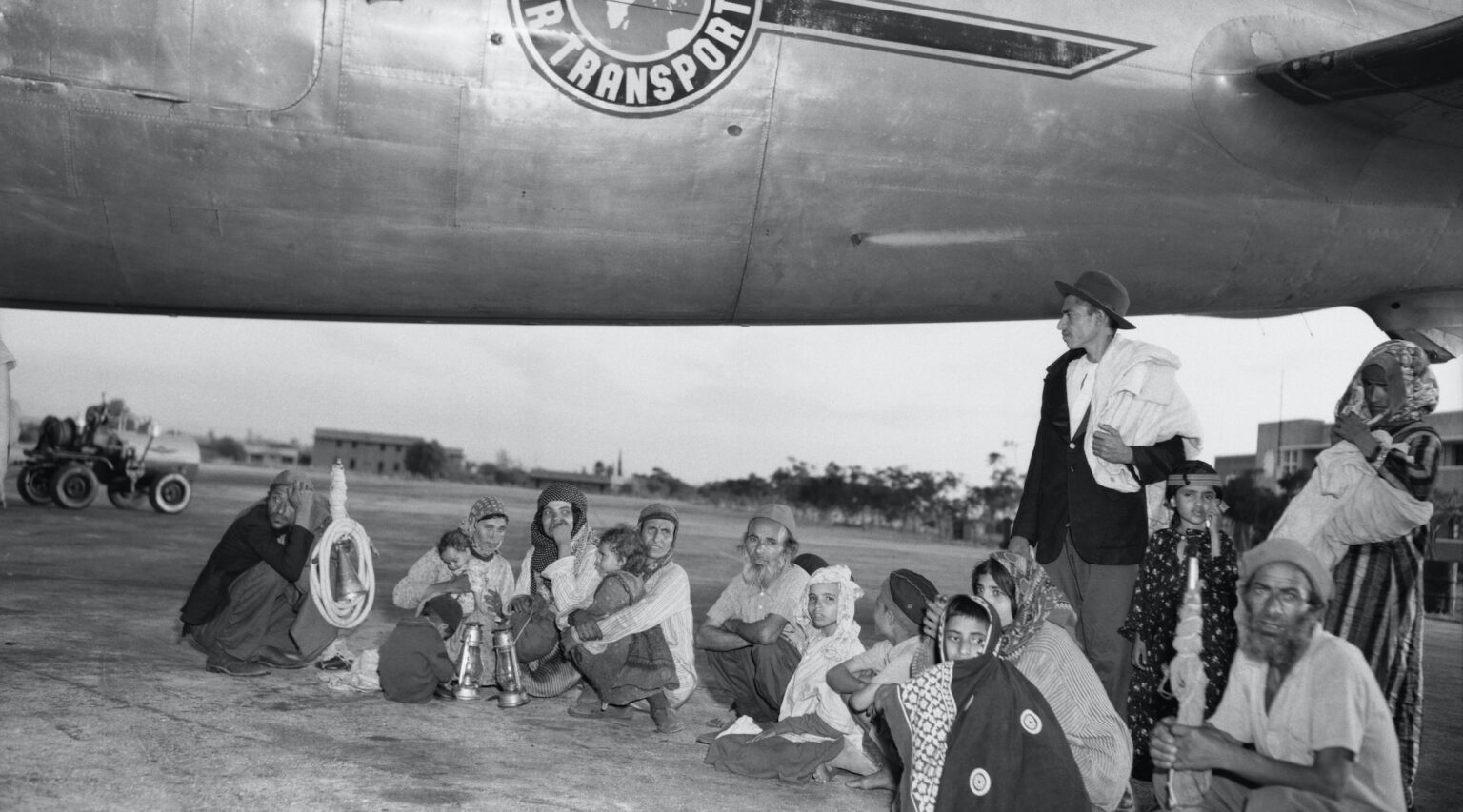 Black and white: A group of men, women and children sit on the tarmac near an old airplane