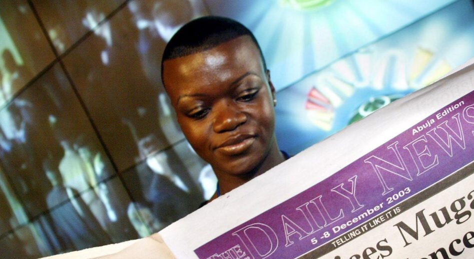 Gugulethu Moyo is seen in 2003 holding a copy of the newspaper where she worked, which was banned by Zimbabwe's government. (Photo/JTA-PA Images via Getty Images)