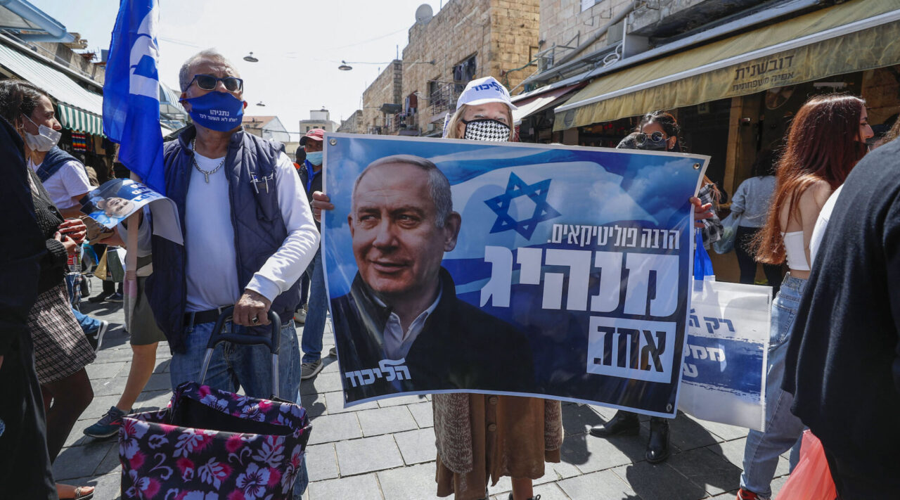 Supporters of Israel's Likud party lift a banner depicting Prime Minister Benjamin Netanyahu during the election campaign at Mahane Yehuda market in Jerusalem, March 19, 2021. (Photo/JTA-Emmanuel Dunand-AFP via Getty Images)
