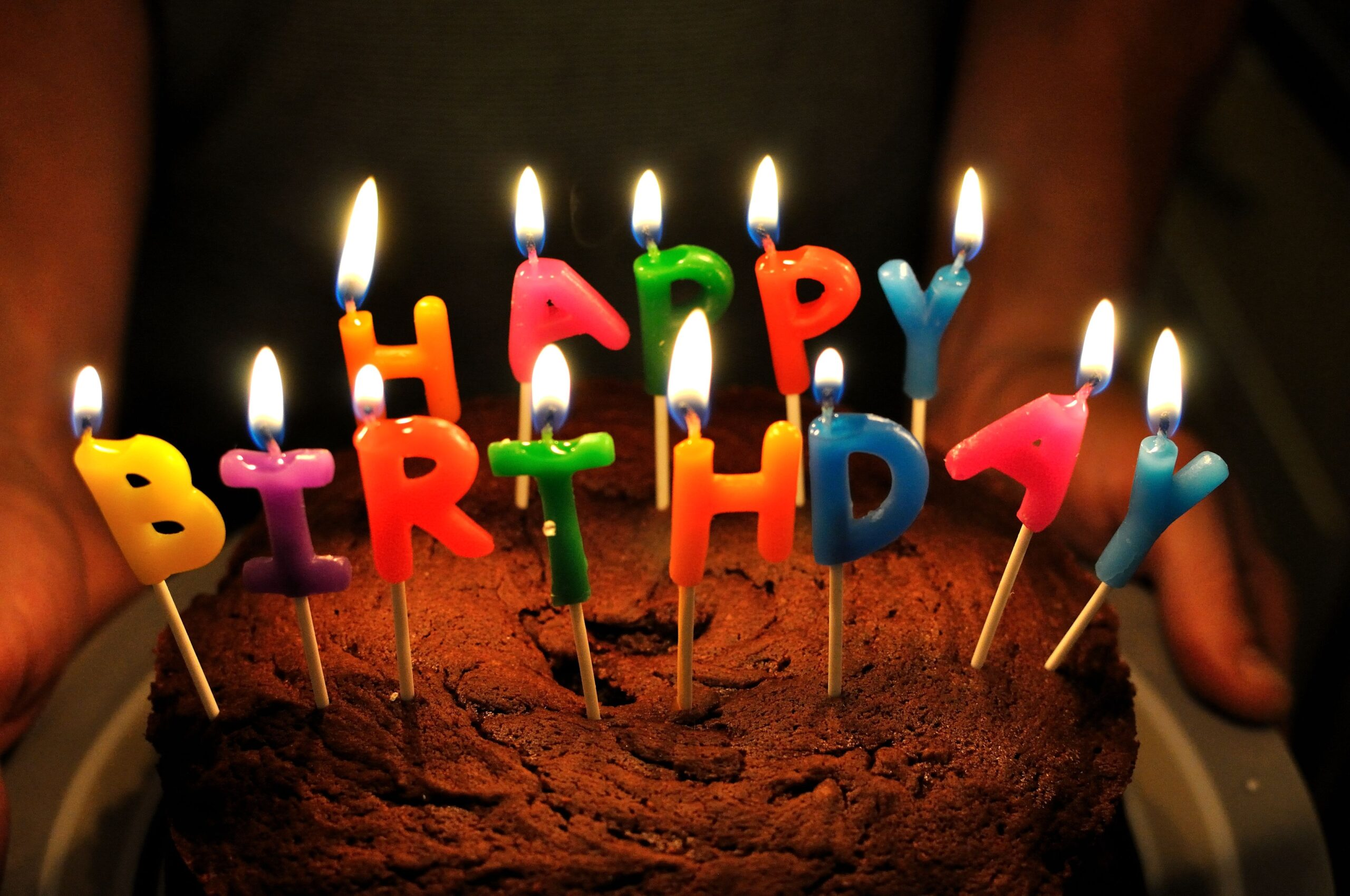 """Photo of a chocolate cake with candles that spell out """"Happy Birthday"""""""