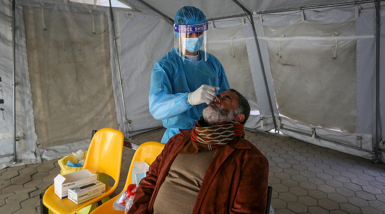 A health worker tests a man for the coronavirus at a health center in Rafah, in the southern Gaza Strip, Feb. 16, 2021. (Photo/JTA-Abed Rahim Khatib-Flash90)