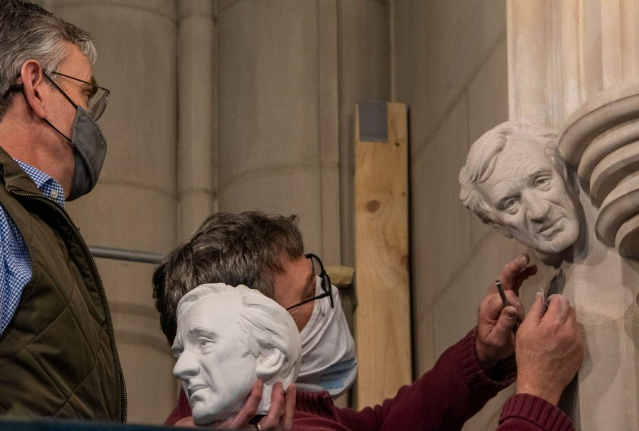 Sculptor Chas Fagan, (left) holds a clay model of a bust of Elie Wiesel and watches as stonemason Sean Callahan (right) uses medieval techniques to carve the bust into the walls of the National Cathedral in Washington, D.C. (Photo/JTA-National Cathedral)
