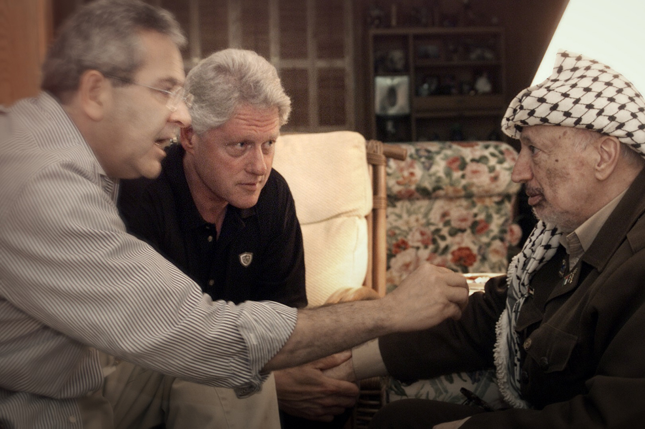 Three older men sit together. Gamal Helal, on the right, points at Arafat, on the left, while talking to him. Bill Clinton sits between them, looking on with intensity.